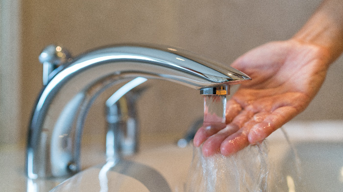 Hand testing water from running faucet